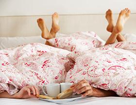 Sexfantasien: Mann und Frau liegen vergnügt unter der Bettdecke